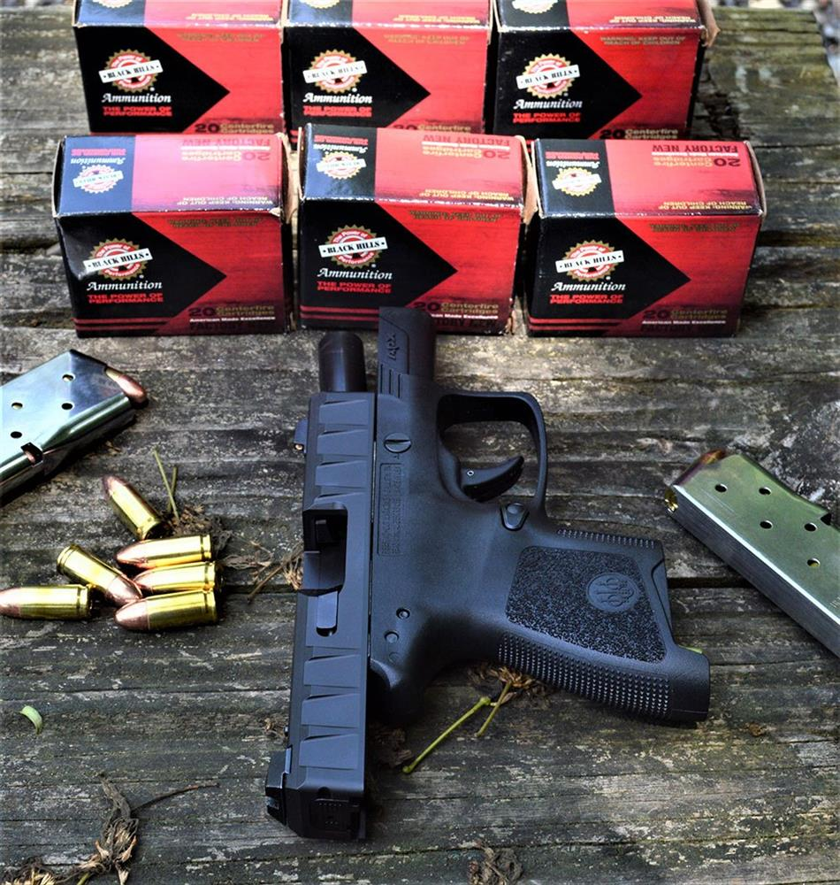 Beretta APX Carry with slide locked back and six boxes of ammunition